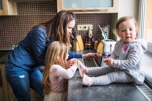 Mãe, com, dela, crianças, usando computador portátil, em, cozinha