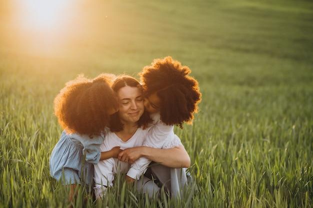 Mãe com dois filhos afro-americanos no campo ao pôr do sol