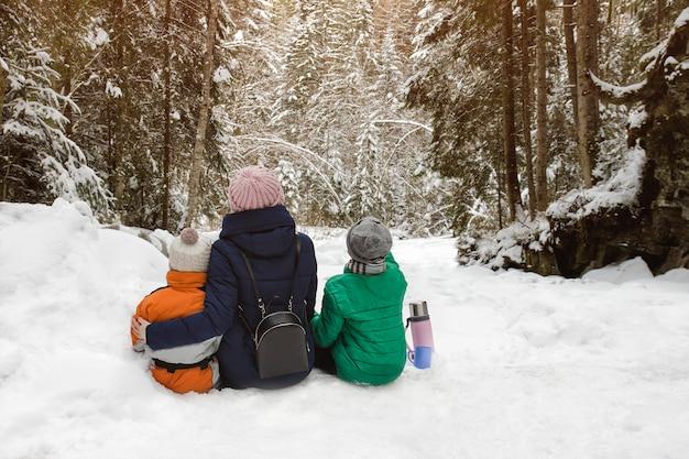 Mãe com dois filhos estão abraçando no contexto da floresta coberta de neve.