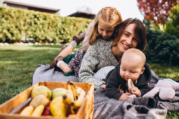Mãe com dois filhos fazendo piquenique em um quintal