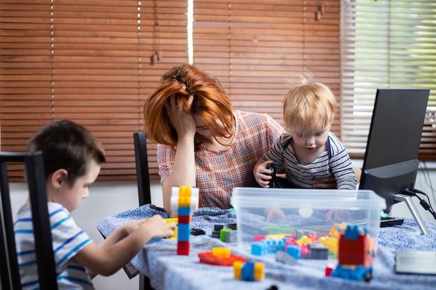 Mãe com dois meninos de joelhos tenta rir em casa.