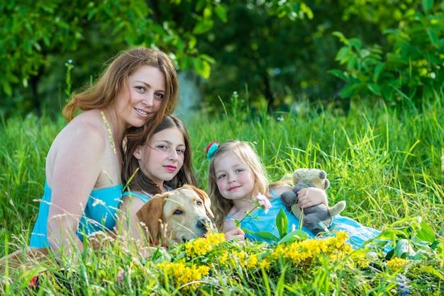 Mãe com duas filhas e cachorro