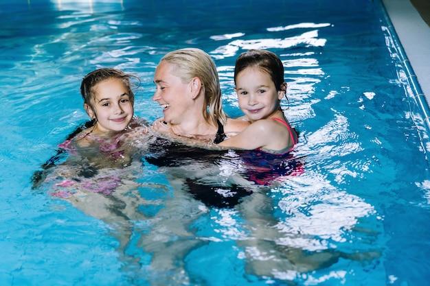 Mãe com duas filhas se divertindo na piscina interior no spa do hotel