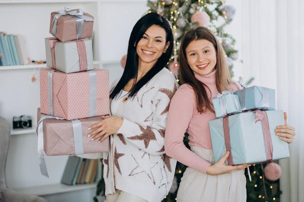 Mãe com filha adulta com presentes de natal por árvore de natal