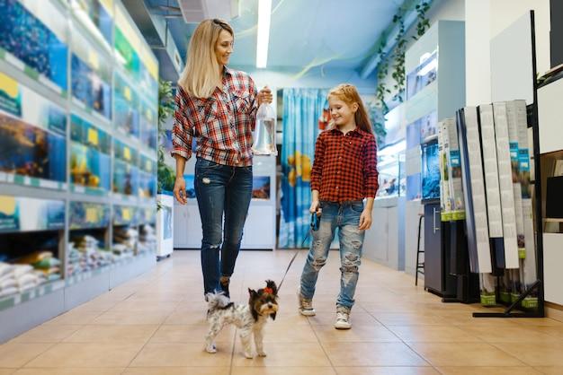 Mãe com filha andando na loja de animais com o cachorrinho. mulher e criança comprando equipamentos em petshop, acessórios para animais domésticos