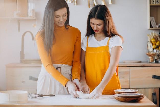 Mãe com filha assando na cozinha