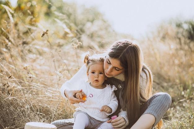 Mãe com filha bebê soprando bolhas de sabão no parque