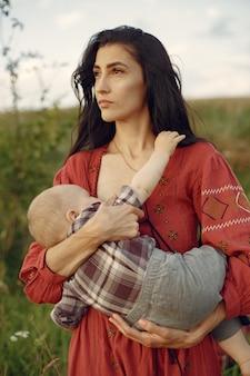 Mãe com filha bonita. mãe amamentando seu filho pequeno. mulher de vestido vermelho.