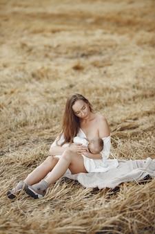 Mãe com filha bonita. mãe amamentando sua filha. mulher de vestido branco.