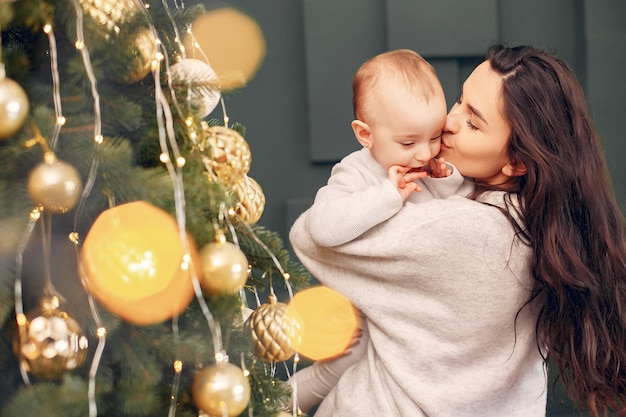 Mãe com filha bonita perto de árvore de natal