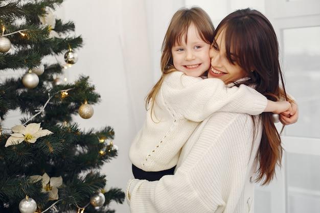 Mãe com filha bonitinha em pé perto de árvore de natal
