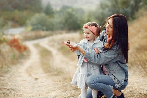 Mãe com filha brincando em um campo com uma borboleta
