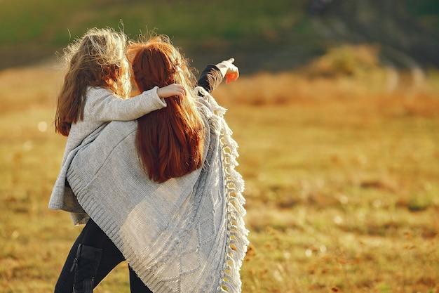 Mãe com filha brincando em um campo de outono