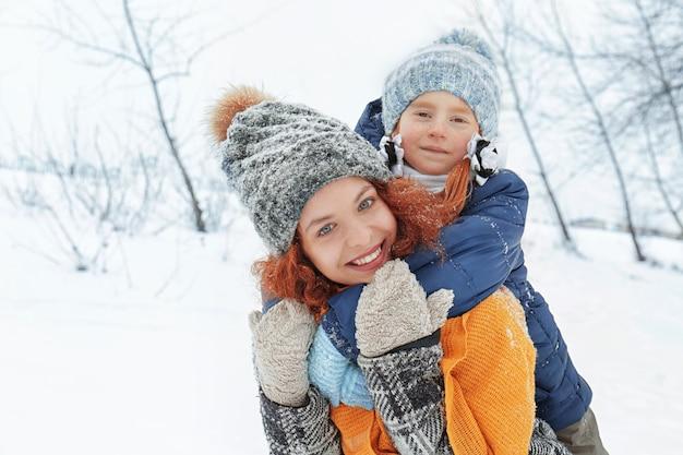Mãe com filha brincando no parque de inverno
