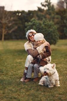 Mãe com filha caminha com um cachorro