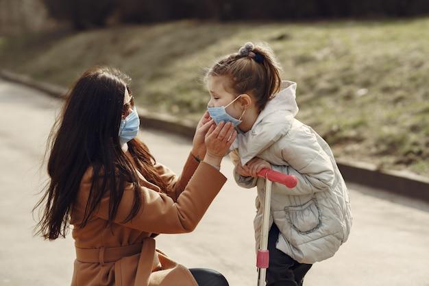 Mãe com filha caminha lá fora em máscaras
