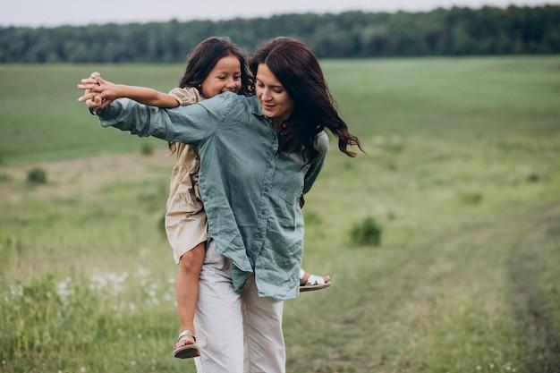 Mãe com filha caminhando juntas no parque