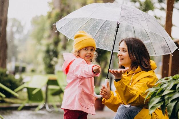 Mãe com filha caminhando no parque na chuva usando botas de borracha
