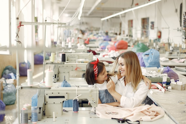 Mãe com filha costurar roupas na fábrica