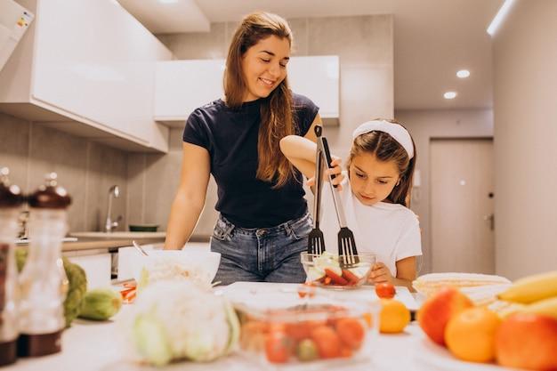 Mãe com filha cozinhar juntos na cozinha