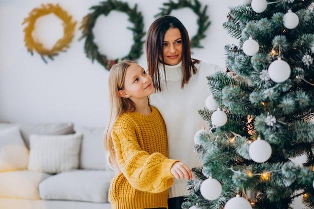 Mãe com filha decorando árvore de natal