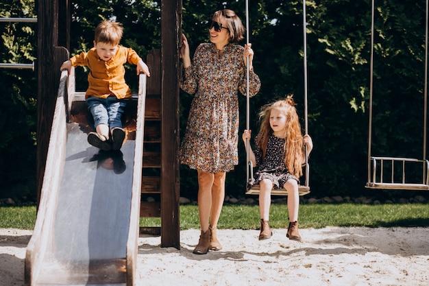 Mãe com filha e filho balançando e deslizando