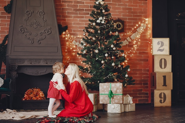 Mãe com filha em casa em um vestido vermelho
