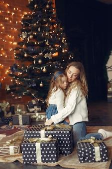 Mãe com filha em casa perto da lareira