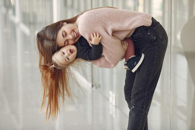 Mãe com filha em pé em um corredor