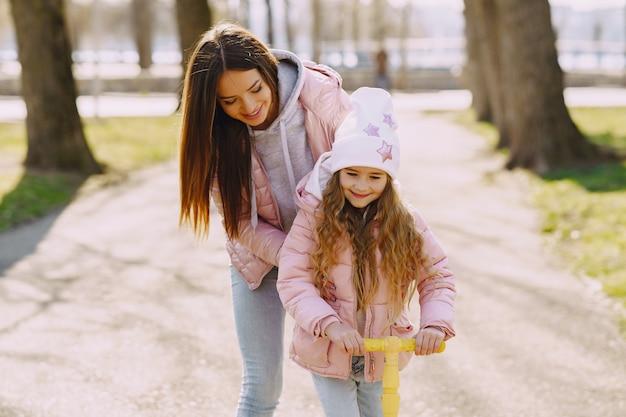 Mãe com filha em um parque com skate