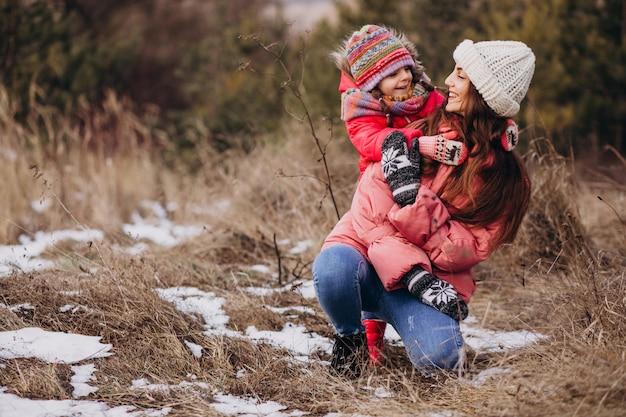 Mãe com filha em uma floresta de inverno