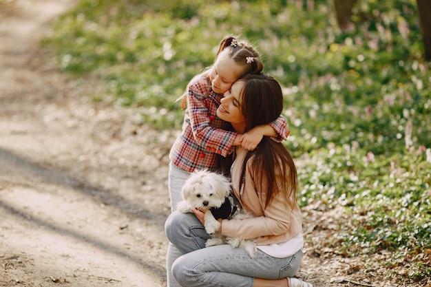 Mãe com filha em uma floresta de primavera com cachorro
