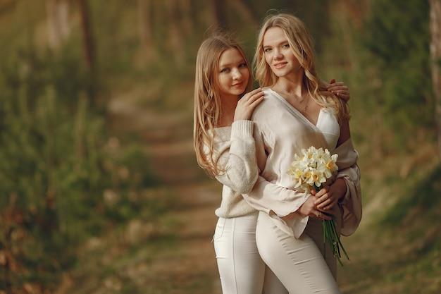 Mãe com filha em uma floresta de verão