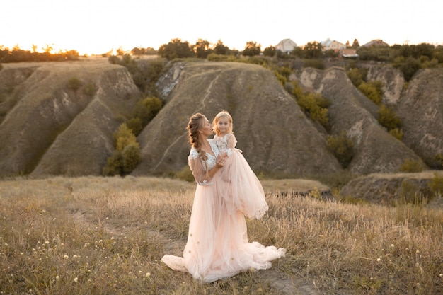 Mãe com filha em vestidos de conto de fadas rosa caminhar na natureza. pequena princesa infância