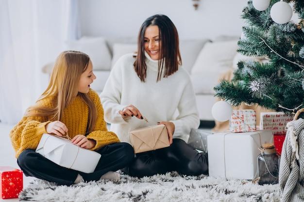 Mãe com filha embalando presentes debaixo da árvore de natal