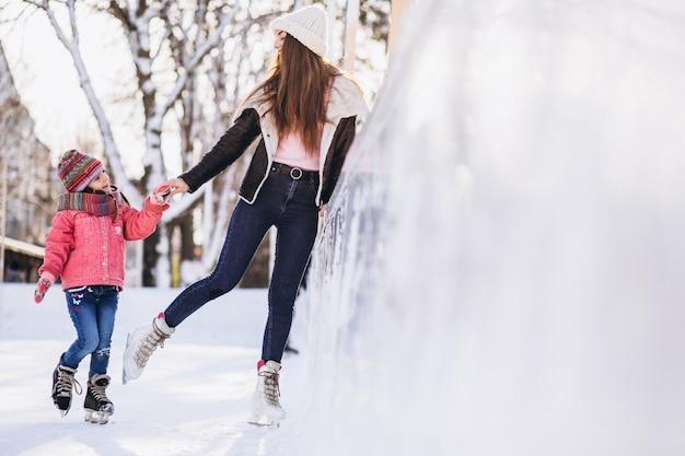 Mãe com filha ensinando patinação no gelo em uma pista