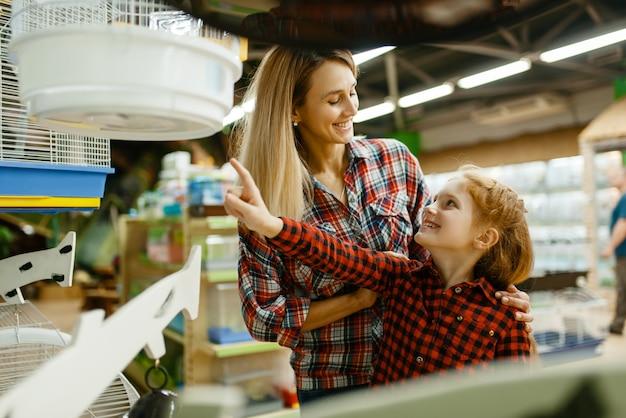 Mãe com filha escolhendo gaiola para pássaros na vitrine na loja de animais. mulher e criança comprando equipamentos em petshop, acessórios para animais domésticos