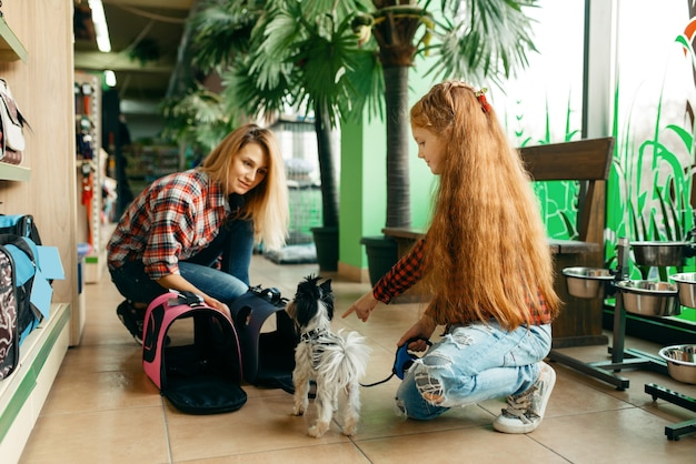 Mãe com filha, escolhendo o saco para cachorrinho na loja de animais. mulher e criança comprando equipamentos em petshop, acessórios para animais domésticos