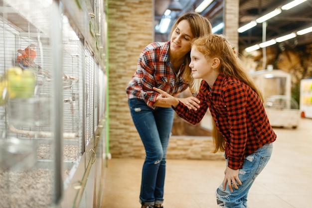 Mãe com filha escolhendo pássaros na vitrine na loja de animais. mulher e criança comprando equipamentos em petshop, acessórios para animais domésticos