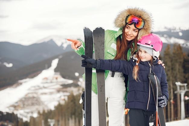 Mãe com filha esquiando. pessoas nas montanhas nevadas.