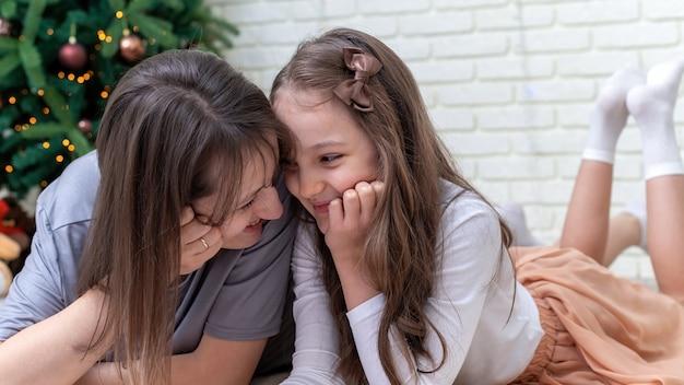 Mãe com filha está sorrindo no chão perto da árvore de natal em casa. ideia de família feliz