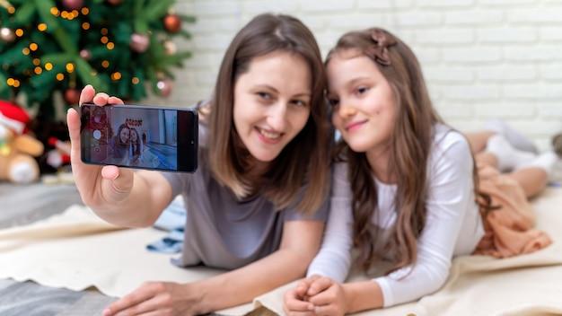 Mãe com filha está tomando selfie no chão perto da árvore de natal em casa. ideia de família feliz