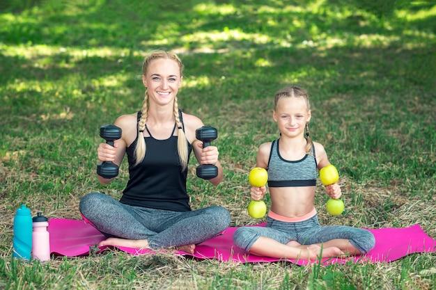 Mãe com filha está treinando com halteres na esteira de rolo no parque