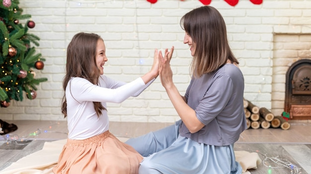 Mãe com filha estão brincando no chão perto da árvore de natal em casa. ideia de família feliz