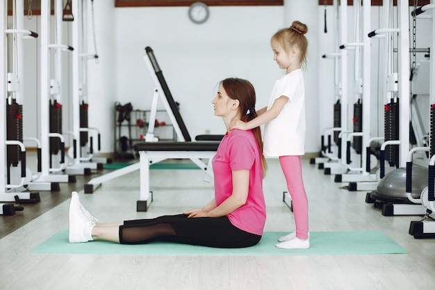 Mãe com filha estão engajados em ginástica no ginásio