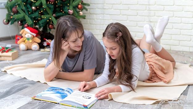 Mãe com filha estão lendo no chão perto da árvore de natal em casa. ideia de família feliz