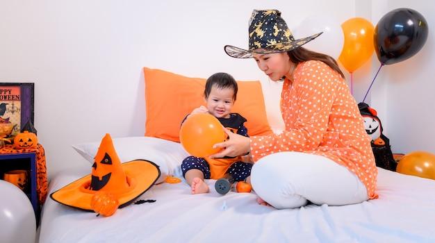 Mãe com filha fantasiada para comemorar o halloween em casa. criança com a mãe na decoração do quarto.