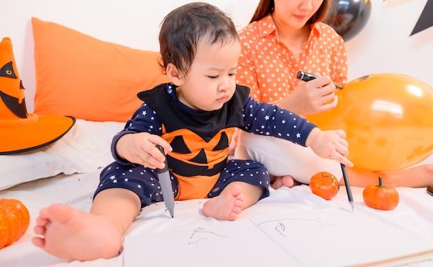 Mãe com filha fantasiada para comemorar o halloween em casa. garoto com a mãe na decoração do quarto na temporada de outono.