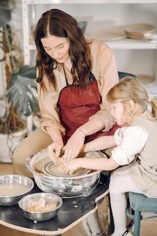 Mãe com filha faz vaso em um potterystudio