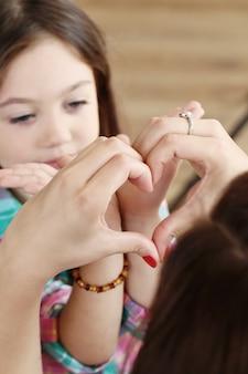 Mãe com filha fazendo corações com as mãos